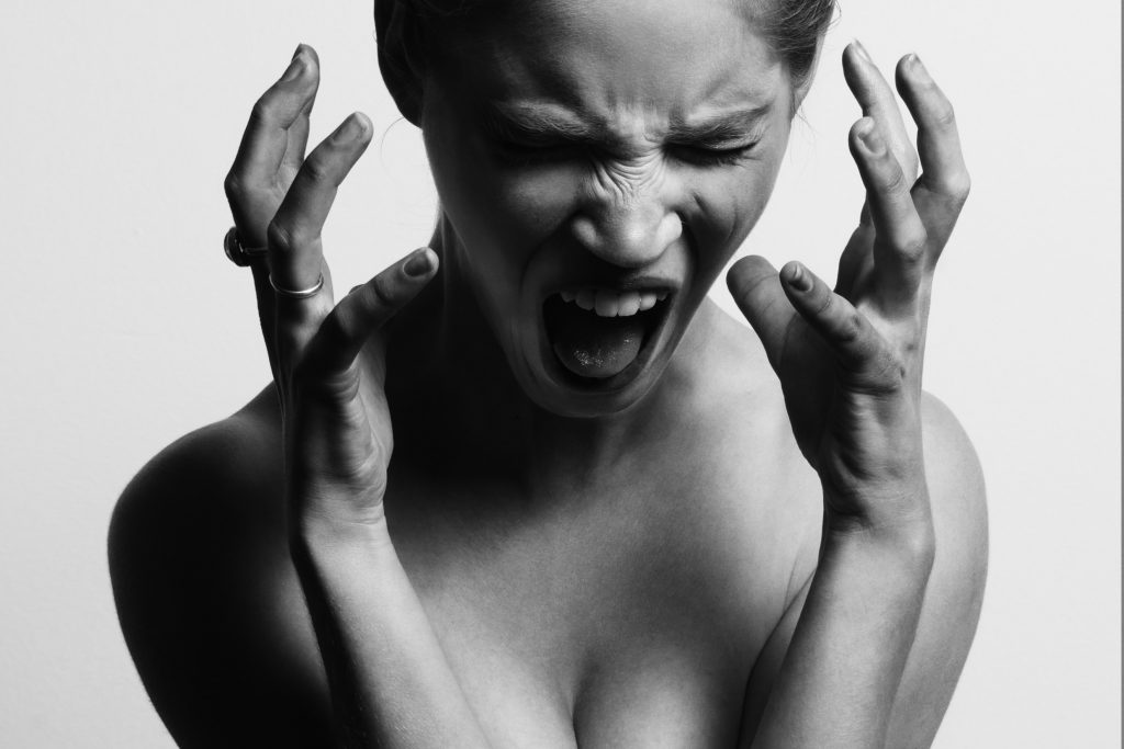 Ung stresset kvinde der skriger i frustration